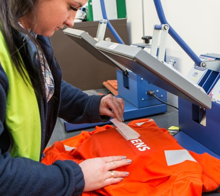 woman printing company logo on arc flash t-shirt
